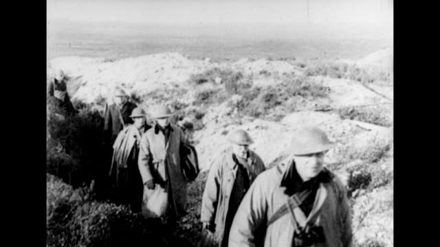 american lawmakers wearing trench coats and helmets walk through a wwi western front battlefield trench / congressmen atop a small hill peer though... - トレンチコート点の映像素材/bロール