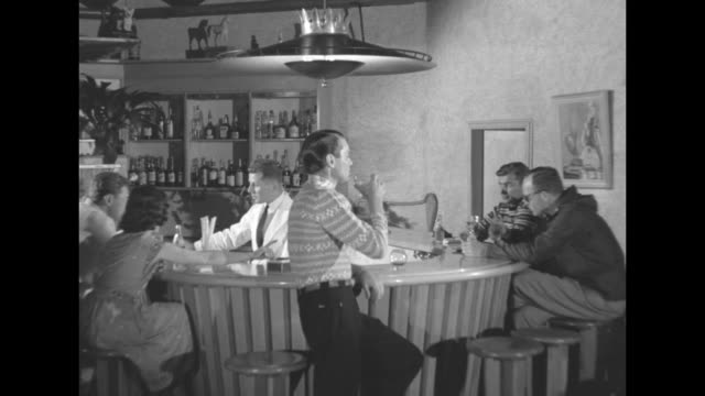 american man seated at swiss bar rises as his companion arrives and they both drain brandy from snifters / note exact day not known - brandy snifter stock videos & royalty-free footage