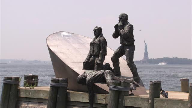 vídeos de stock, filmes e b-roll de ws, american merchant mariners memorial with statue of liberty in distance, battery place, new york city, new york, usa - figura feminina