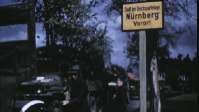 american military convoy driving down the road and close up of german sign for the city / nuremberg, bavaria, germany - baviera video stock e b–roll