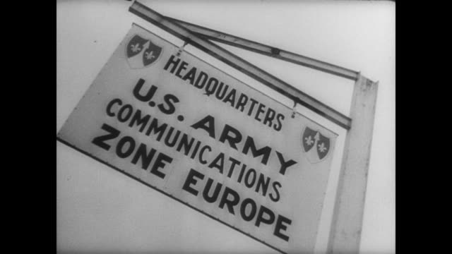 CU American military policeman directing traffic at military installation in France / CU sign reading 'HEADQUARTERS US ARMY COMMUNICATIONS ZONE...