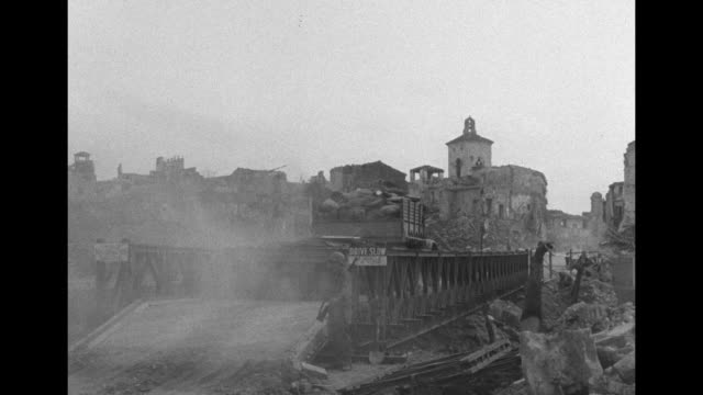 vídeos de stock, filmes e b-roll de american military truck and trailer drives over bridge with damaged lamppost at left and destruction beyond / vs views of town across bridge / jeep... - world war ii