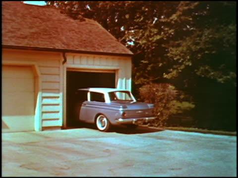 american motors rambler twodoor sedan backs out of a suburban garage camera follows as car backs out onto a suburban road so that front of car is... - sedan stock videos & royalty-free footage