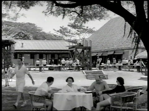 american people lounging around country club house at tables by pool ws people sitting at tables congregating ms people in poolwear sitting talking... - zurücklehnen stock-videos und b-roll-filmmaterial