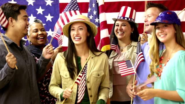 stockvideo's en b-roll-footage met american people wave flags at political rally, convention. - politieke bijeenkomst