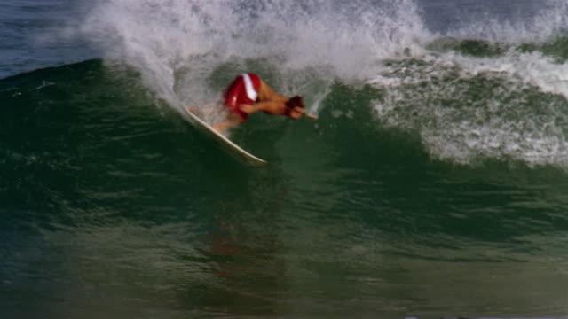 american pro surfer damien hobgood carving a turn at backdoor pipeline / north shore, oahu, hawaii - badeshorts stock-videos und b-roll-filmmaterial