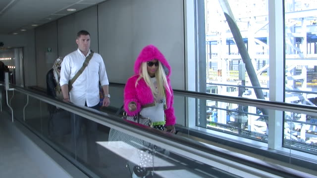 american rapper and songwriter nicki minaj flies into heathrow ready for a london concert. wearing a distinctive pink, hooded jacket she walks... - songwriter stock videos & royalty-free footage