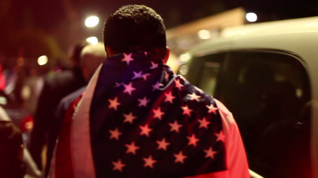 stockvideo's en b-roll-footage met american soccer fan with flag as cape from behind - verenigde staten