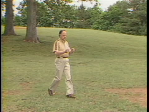american society of dowsers president george glenn demonstrates and explains dowsing. hand held shot of him holding two l shaped dowsing rods while... - bending over stock videos & royalty-free footage