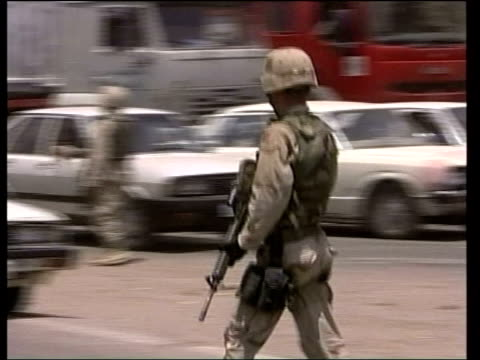 american soldier along past burntout vehicle in road ms group of american soldiers on duty beside main road ms american soldier holding rifle ms... - al fallujah stock videos & royalty-free footage
