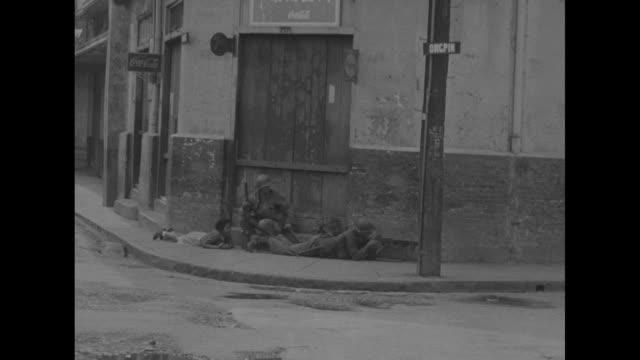 american soldier peers thru slit, aims rifle / mls looking down thru slit to dead soldier lying on sidewalk below / two us soldiers with mounted... - hängen stock-videos und b-roll-filmmaterial