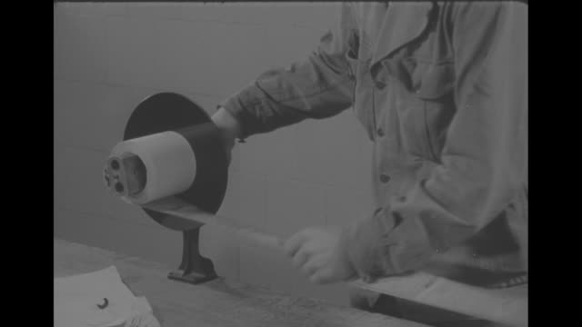 vs american soldier stands at huge mound of mail sacks and looks through film / vs technician loads film onto large roller of machine / vs vmail on... - postal stamp stock videos and b-roll footage