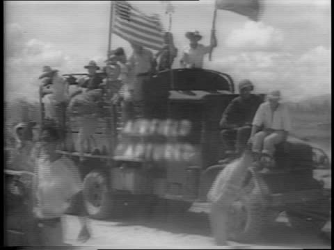 American soldiers and Filipinos jump down from a truck with flags / soldiers mill around the airstrip while a line of fighter planes fly overhead /...