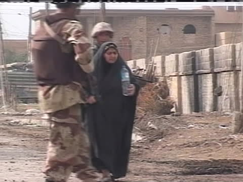 american soldiers assist an iraqi family down a war-torn street in iraq. - (war or terrorism or election or government or illness or news event or speech or politics or politician or conflict or military or extreme weather or business or economy) and not usa stock videos & royalty-free footage