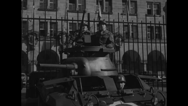 stockvideo's en b-roll-footage met vs american soldiers atop a tank turret against the iron fence of nuremberg's palace of justice where the nuremberg trials are being held two flatbed... - 1946