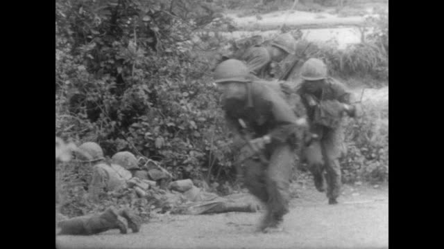 american soldiers crossing the land near bong son airbase under attack from viet cong snipers / soldiers lay on ground to shoot / soldiers crouch... - dragging stock videos & royalty-free footage