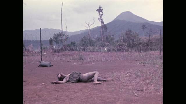 american soldiers examine the barbed wire defenses that surrounded their small artillery base and the bodies of some of the north vietnamese... - cadavere video stock e b–roll