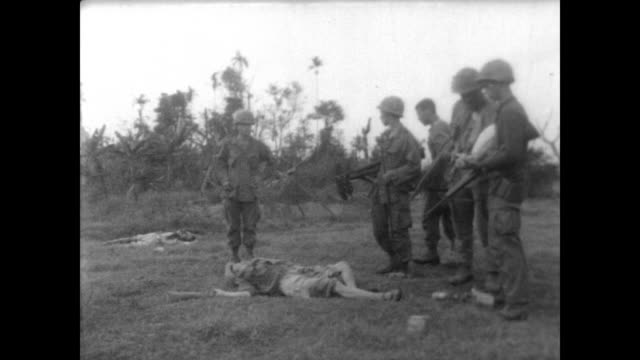 American soldiers in a jungle village in Vietnam during Operation Pershing / village refugees evacuating / soldiers mill about the dead bodies of...