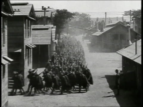american soldiers marching in long formation down dirt street town or barracks soldiers on horseback leading troops in rain gear through mud soldiers... - 1918 stock videos and b-roll footage