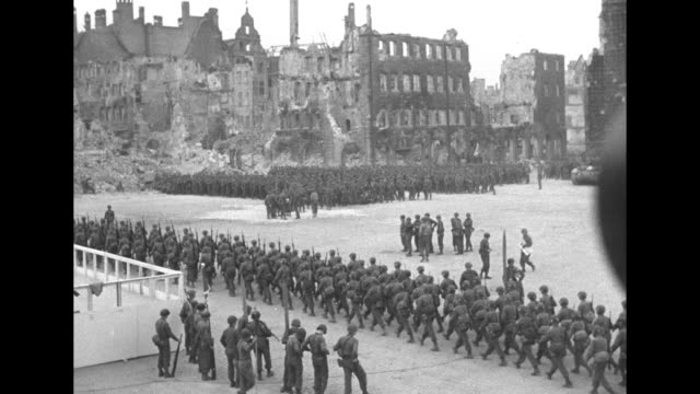 american soldiers marching through ruins of nuremberg / vs men marching past reviewing stand at zeppelin field with officers on platform with bronze... - covering stock videos and b-roll footage