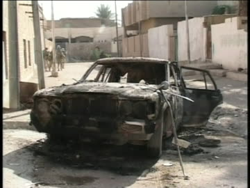 american soldiers patrol a street near a burned-out car in iraq. - conflict stock videos & royalty-free footage