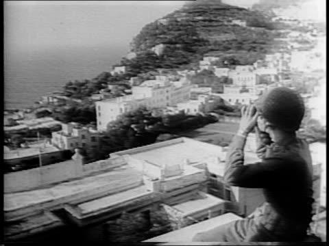 american soldiers ride tank down dirt road / soldier looking through binoculars on isle of capri italy / camera pans coast back to soldier / ships... - harbour stock videos & royalty-free footage