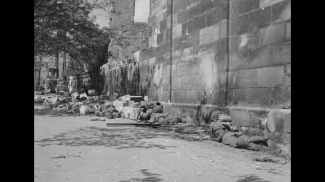 vidéos et rushes de american soldiers run through open areas in nuremberg and lay prone / a tank drives past skeleton of ruined buildings / soldiers firing mortars in... - ruiné