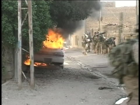 american soldiers rush past a burning car in iraq. - (war or terrorism or election or government or illness or news event or speech or politics or politician or conflict or military or extreme weather or business or economy) and not usa stock videos & royalty-free footage