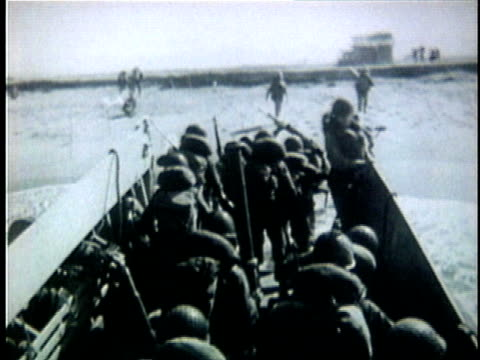 american soldiers storm beach at danang from landing craft during the vietnam war / south vietnam - ダナン点の映像素材/bロール