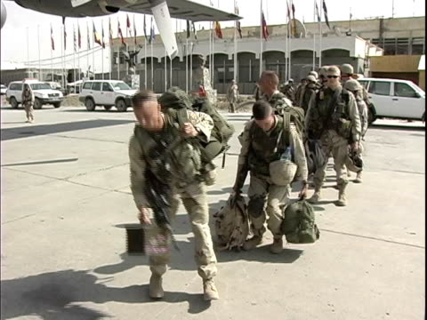 American soldiers waiting in line to board military airplane on runway / Afghanistan