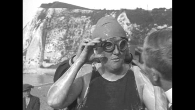 american swimmer gertrude ederle stands on the beach at cap griznez as an aide coats her body with lanolin she dons a pair of goggles with white... - gertrude ederle stock videos & royalty-free footage