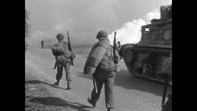 VS American tanks and United States 3rd Army soldiers pass a smoke generator / halftrack passes / white surrender flags hang from upper windows of...