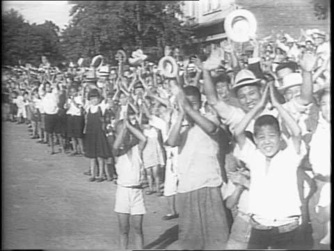 vídeos y material grabado en eventos de stock de american troops marching down street in korea, entering kyongsong / a crowd gathered on the side of the street, watching the troops / crowds clapping... - coreano oriental