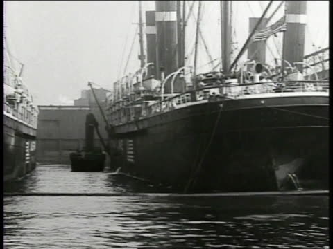 American US flag painted on side of Merchant ship PAN Harbor w/ ships docked MS President Woodrow Wilson sitting at desk writing on bottom of paper