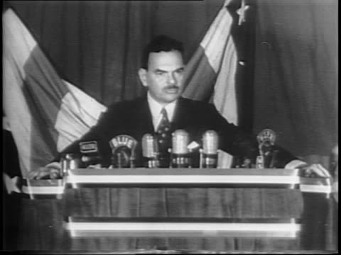 american voters cast ballots in crowded room / closeup ballots inserted into slot of ballot box / thomas dewey headshot with a backdrop of a rally /... - anno 1944 video stock e b–roll