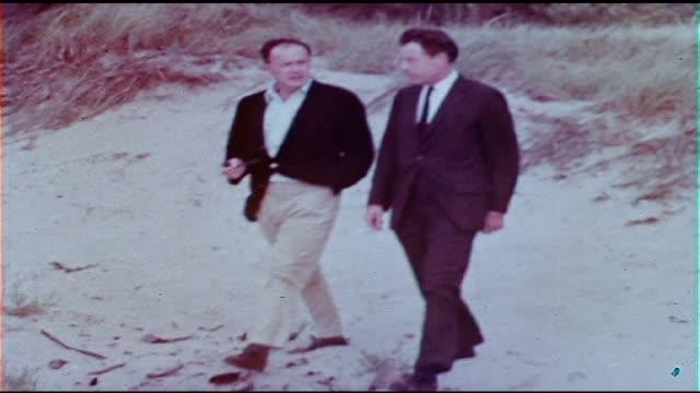 american writer and director joseph l mankiewicz walking along beach talking with time-life correspondent robert copland - ジョセフ・l・マンキーウィッツ点の映像素材/bロール