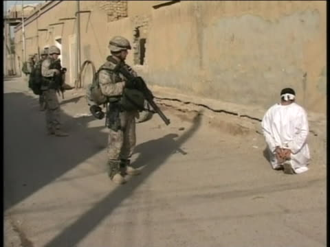 americans guard a blindfolded captive in iraq. - (war or terrorism or election or government or illness or news event or speech or politics or politician or conflict or military or extreme weather or business or economy) and not usa stock videos & royalty-free footage