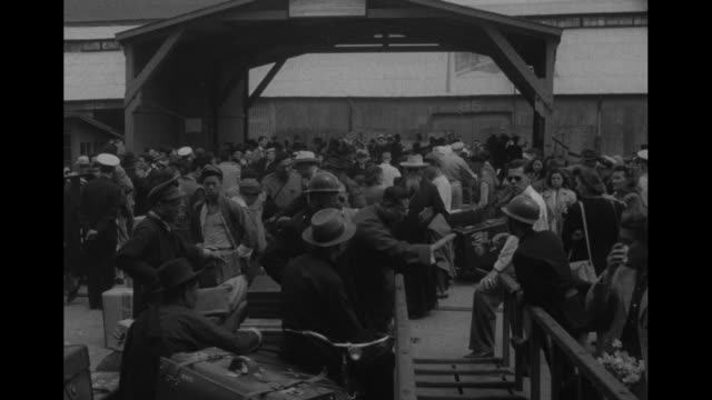 vidéos et rushes de americans' papers are checked at table / pan people stand on docks including a priest / cu woman holding a baby steps onto gangplank other women... - guerre civile
