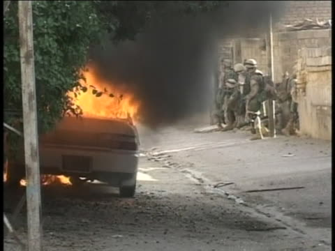 american-soldiers on foot-patrol near burning car in iraq. - (war or terrorism or election or government or illness or news event or speech or politics or politician or conflict or military or extreme weather or business or economy) and not usa stock videos & royalty-free footage
