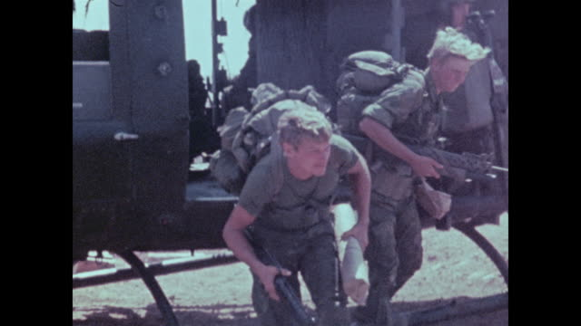 amid purple smoke hueys approach landing zone and pause while soldiers of the 101st airborne with heavy rucksacks jump out. - vietnam war stock videos & royalty-free footage