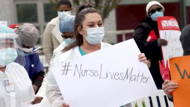 amid the outbreak of the coronavirus disease public and private hospital nurses and medical practitioners rally outside jacobi medical center... - schutz stock-videos und b-roll-filmmaterial
