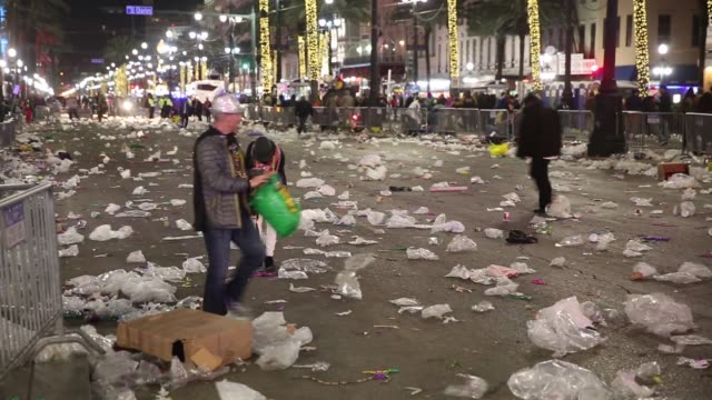 amid trash blowing across canal street avenue revelers pick up abandoned beads at the bacchus parade during mardi gras in new orleans louisiana - gras stock videos and b-roll footage