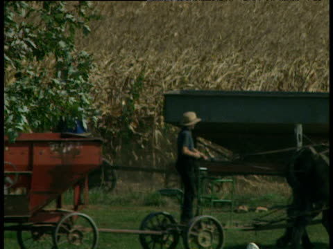 Amish farmers on horse drawn farm equipment Lancaster County