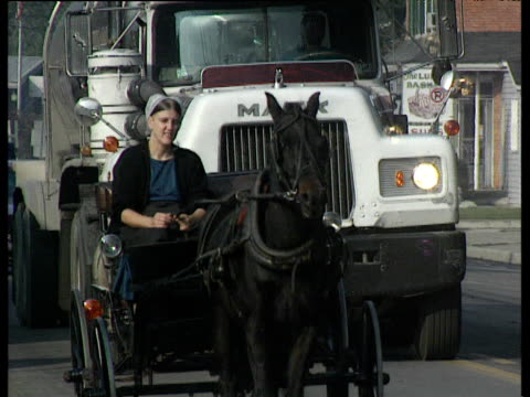 vídeos de stock e filmes b-roll de amish lady in open horse drawn carriage being overtaken by large tanker pennsylvania - amish