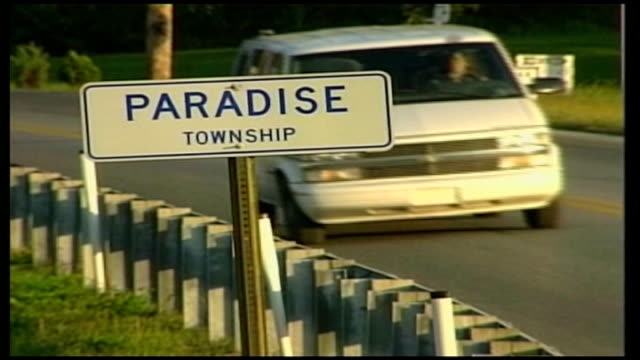 Gunman named as Charles Carl Roberts USA Pennsylvania Lancaster County EXT Sign 'Paradise Township' Sun shining in sky above farmland and fields at...