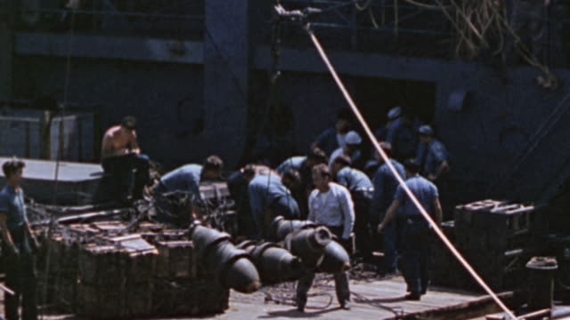 ammunition transport ship alongside u.s. navy warship during world war ii, with sailors bringing general purpose bombs aboard via net and hawser /... - world war ii video stock e b–roll
