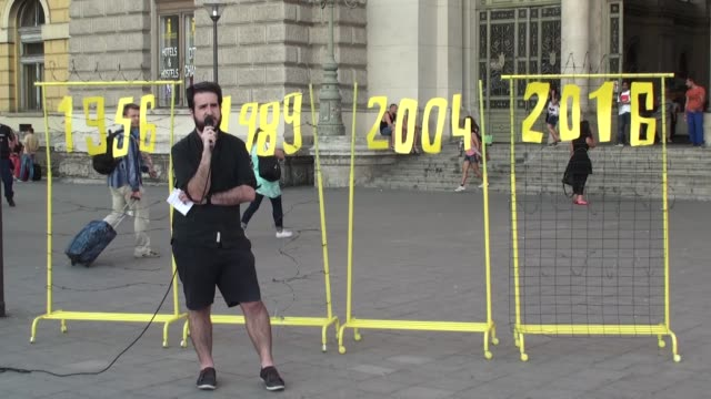 amnesty international activists attend a protest on the first anniversary of the closure of hungarianserbian border with fences to prevent the flow... - amnesty international stock videos & royalty-free footage