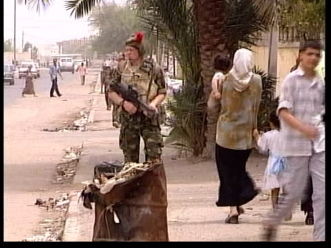 Amnesty International allegations against British troops ITN Basra British troops along street on patrol CMS British soldier surrounded by Iraqi...