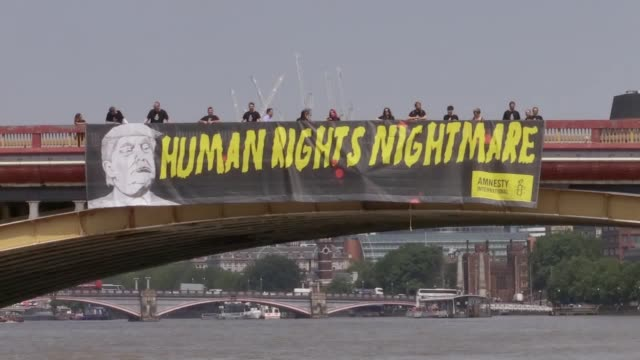 amnesty international unfurl a banner on a bridge over the thames, opposite the us embassy, and bearing the words 'human rights nightmare'... - human face video stock e b–roll