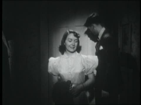 b/w 1951 amorous teen couple entering house / almost kiss but are interrupted by noise off screen - 1951点の映像素材/bロール